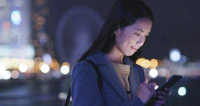 Young Woman look at mobile phone in city at night