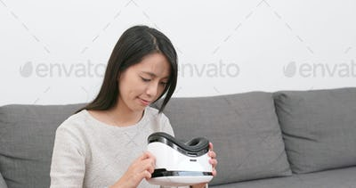Woman looking though VR device at home