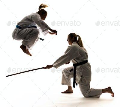 Two women athletes training karate in jumping