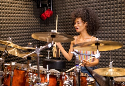 Laughing vivacious young woman playing drums