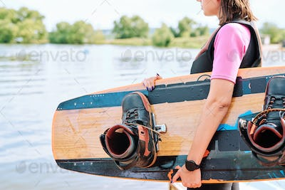 Active young surfer in sportswear holding surfboard while standing by waterside