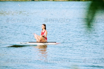 Young serene female in red swimsuit sitting on surfboard in pose of lotus