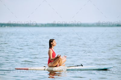 Young sportswoman in red swimsuit practicing yoga while sitting on surfboard