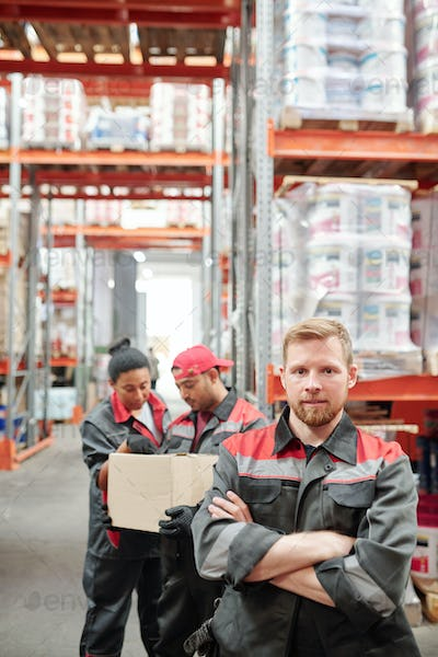 Bearded man in workwear standing in front of camera on background of colleagues