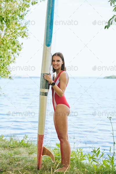 Young cheerful brunette woman in red swimwear standing by water with surfboard