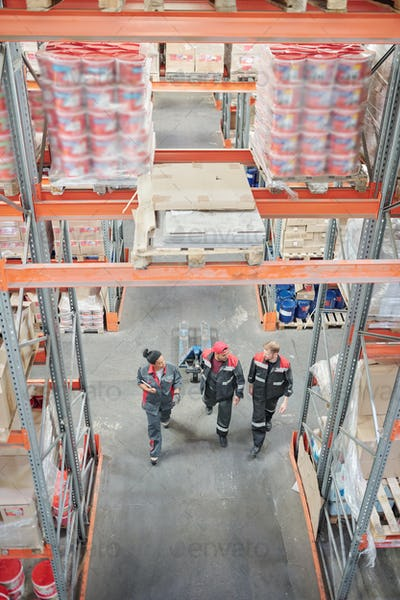 Three intercultural warehouse workers in uniform discussing working questions