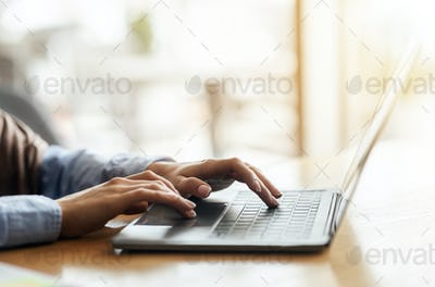 Female hands typing on laptop over blurred background
