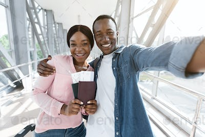 Traveling Together. Happy african couple taking selfie in airport, waiting for boarding