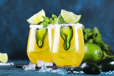 Spicy margarita cocktail with tequila, mango juice, jalapeno pepper, lime and salt, blue background