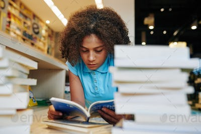 Teenage girl reading students book