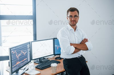 Young businessman in formal clothes is in office with multiple screens