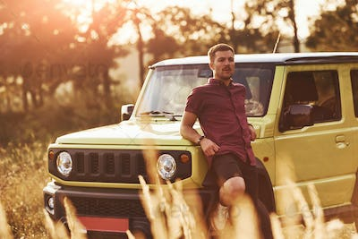 Portrait of man that leaning on green car at beautiful sunny day outdoors in the field