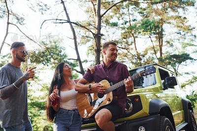 Friends have nice weekend outdoors near theirs green car with acoustic guitar