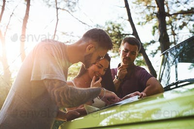 Young friends reading map that is on the hood of modern green jeep in the forest