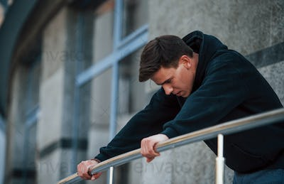 Young man leaning on the silver colored railings. Feels tired