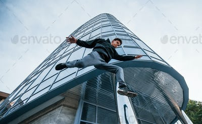 Young man doing parkour in the city at daytime. Conception of extreme sports