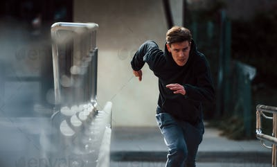 Front view of young runner in black clothes that is in the city