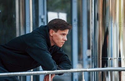 Portrait of young main in black clothes that leaning on the railings and taking a break
