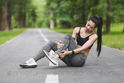 Sports Injury. Asian Girl Suffering From Ankle Pain After Jogging In Park