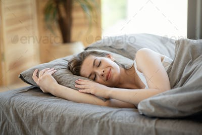Relaxed millennial girl sleeping on comfy pillow in bed, indoors