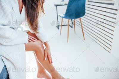 Cropped photo of woman in white clothes that sits on the bed in room. Nice lighting