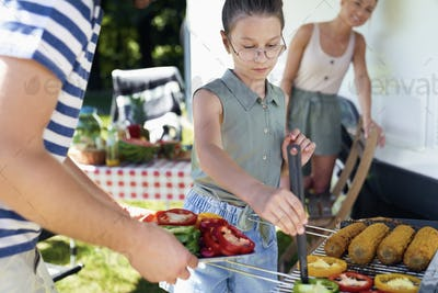 Daughter helping mother in preparing barbecue meals
