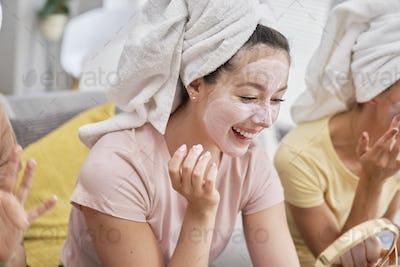 Girls having fun while applying a facial mask