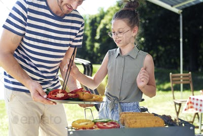 Father and daughter serving vegetables on barbecue grill