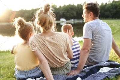 Family watching sunset by the lake