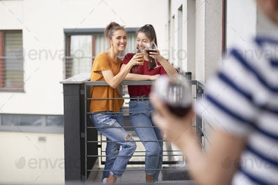 Friends having home party on balcony