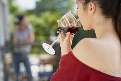 Rear view of woman drinking wine outdoors