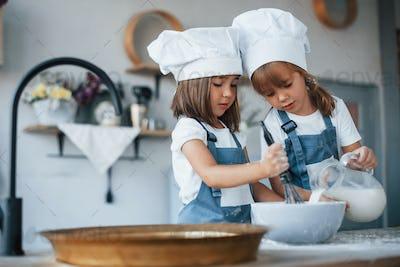 Family kids in white chef uniform preparing food on the kitchen