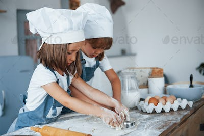 Concentrating at cooking. Family kids in white chef uniform preparing food on the kitchen