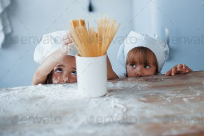 Having fun with spaghetti. Family kids in white chef uniform preparing food on the kitchen