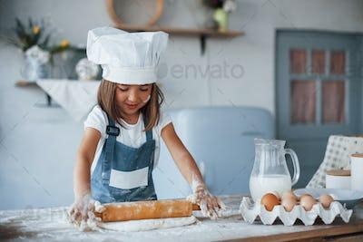 Cute kid in white chef uniform preparing food on the kitchen