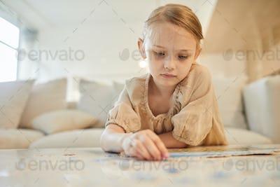 Cute Girl Solving Jigsaw Puzzle