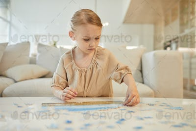 Little Girl Solving Jigsaw Puzzle