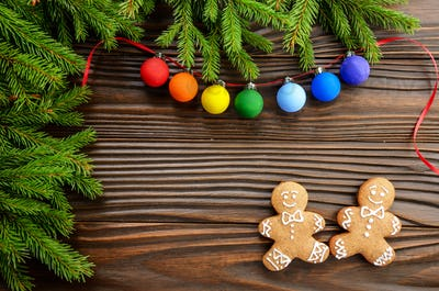 Christmas background of gingerbread cookies spruce branches and colorful balls on wooden table