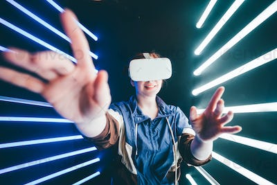 Girl using VR goggles in colorful neon lights, having fun.