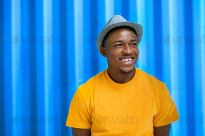 Cheerful young black man standing against blue background, black lives matter concept