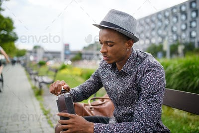 Cheerful young black man commuter sitting on bench outdoors in city