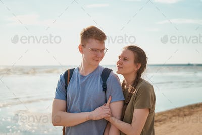 Millennial couple embracing and posing on beach on sunny day
