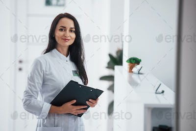 Portrait of brunette doctor with notepad in hands that stands indoors at clinic