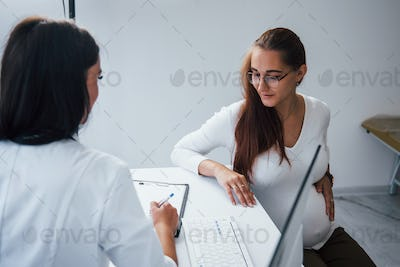 Pregnant woman have consultation with obstetrician indoors