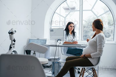 Active conversation. Pregnant woman have consultation with obstetrician indoors