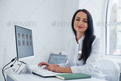 Brunette female doctor sits in modern office by computer and looks at camera