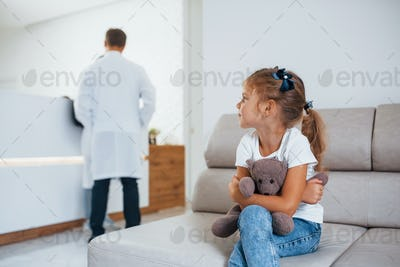 Doctors behind. Cute little girl with teddy bear in hands sits in waiting room of hospital