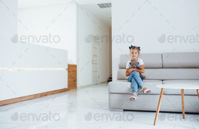 Cute little girl with teddy bear in hands sits in waiting room of hospital