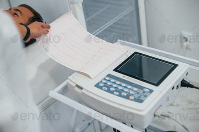 Man lying on the bed in the clinic and getting electrocardiogram test