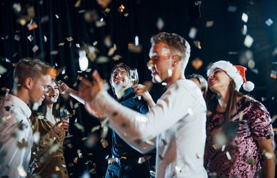 Confetti is in the air. Group of cheerful friends celebrating new year indoors with drinks in hands